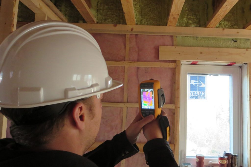 A person using an infrared camera to perform a home energy evaluation
